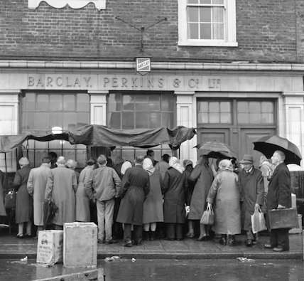 People crowding round a row of covered stalls on a rainy day. c.1955