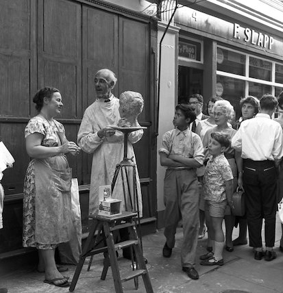 Group of people watch a sculptor. c.1955