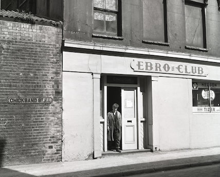 A young man stands in the doorway of the Ebro Club. c.1955