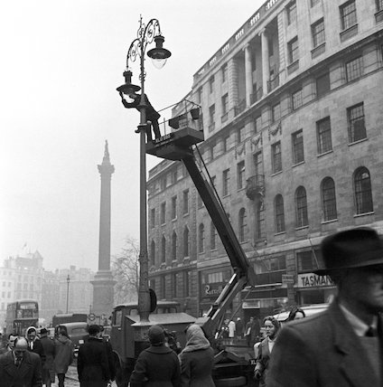 A man changes the bulb in a streetlamp. c.1955