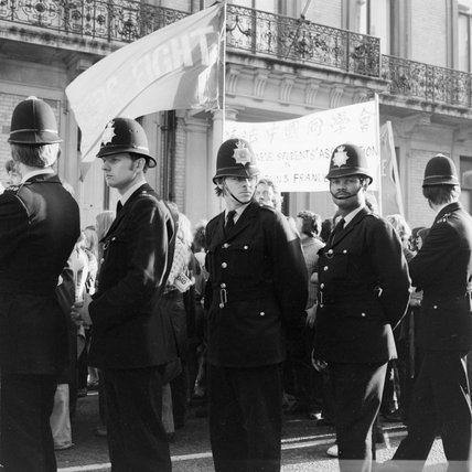 A line of policemen  at a demonstration in London; 1955