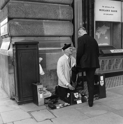 Vincent St George shining the shoes of a city worker; 1963