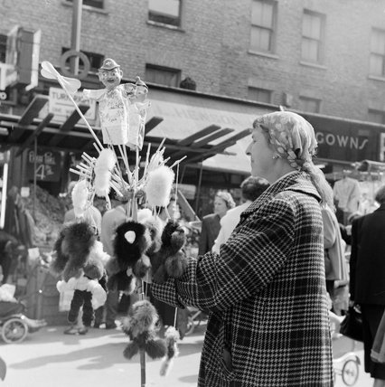 Trader selling puppets in a London street. 1955