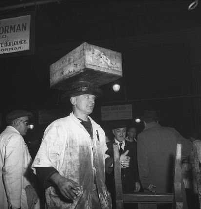 Man carrying a box on his head, Billinsgate market: 20th century