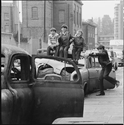 Four boys play on wrecked cars parked in the street: 1967