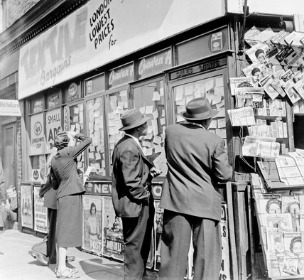 Browsing advertisements in a shop window: 1955