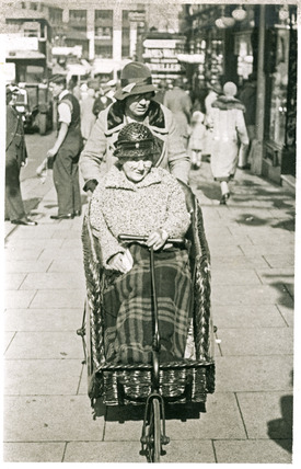 Elderly woman in a bathchair, Sutton High Street: 20th century