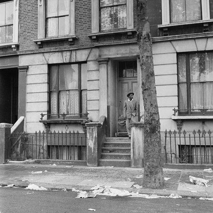 A man on the doorstop of terraced house, Kensington: 20th century