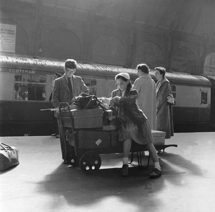 Girl sat with luggage on the platform at Kings Cross Station: 1955