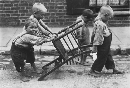 Four boys playing with a chair: c.1900