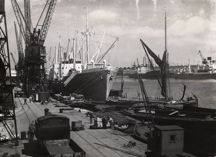 A ship discharging timber on the Thames; 1947