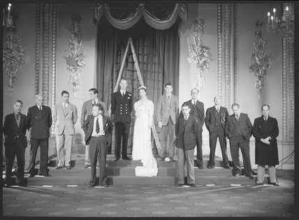 Thirteen unknown sitters in set-up photograph for the portraits of Queen Elizabeth II and Prince Philip with their wedding guests