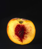 A peach, cut in half to show the stone, 1990s.