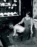 A Welsh miner's wife washing her husband after work, June 1931.