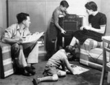 Mother, father and two sons listening to the radio and reading, c 1940s.