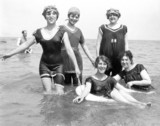 Five women paddling in the sea, one of whom