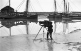 Photographer standing on an estuary mudflat taking a photograph, c 1900s.