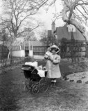 Girl with a pram full of dolls, c 1910s.