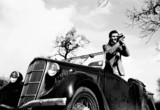Man standing in a Ford motor car, filming with a cine camera, c 1930s.