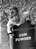 Small boy holding a toy gun inside a box ma