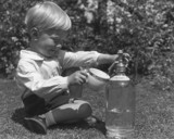 Small boy pouring himself a drink from a so