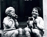 Two boys sitting on a doorstep eating bread and jam, c 1920s.