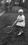 Small child holding a large tennis racket, c 1920s.
