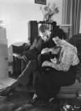 Young couple relaxing at home with a cat, c 1930s.