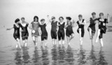 Line of women in bathing costumes paddling