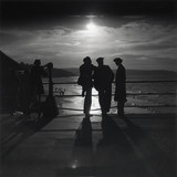 Figures silhouetted by the moon on a promenade, c 1930s.