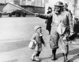 Child and warden wearing gas masks, London, 27 March 1941.
