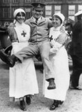 Two female nurses lifting a soldier who was a former patient, 1914-1918.