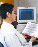 Molecular geneticist analysing the output of a DNA sequencer, May 2000.