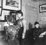 Three woman in a drawing room, c 1890s. Two