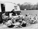 Camping Club member realxing outside caravan, c 1950s.