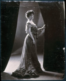 Woman in evening gown holding open a curtain, c 1900.