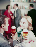 Couple drinking beer, c 1950s.