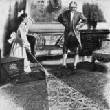 Maid vacuum cleaning a carpet while a manservant looks on, 1911.