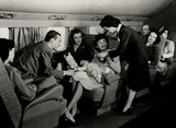 Air hostes attending to a family with a baby during a flight, c 1950s.