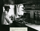 The steward prepares lunch in the galley of an Imperial Airways Scylla, 1934.