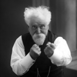 Sir Hiram Maxim with his fists raised, c 1900.