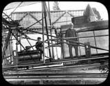 Maxim standing on the framing of his 1894 machine outside the hangar, 1894.