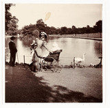 Woman and wheelchair in a park, c 1900.