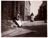 Women talking on a doorstep, c 1900.