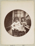 Two children sitting in a wicker chair outside their house, c 1890s.