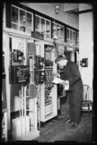 Man checking an automatic telephone exchange, 1933.
