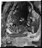 Tin miners taking lunch underground, 1933.