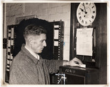 Weaver clocking on at the start of his shift, Wigan, November 1955.