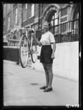 Woman holding a lightweight bicycle, 1934.
