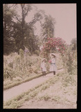 Two girls on a path carrying flowers, 1908.